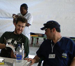 Dr Paul Kelly, Consultant in Emergency Medicine, Wexford General & Waterford Regional Hospitals (Right) receiving a handover from colleague Dr Michael Sweeney at their makeshift clinic in Port-au-Prince, Haiti on 11th February 2010
